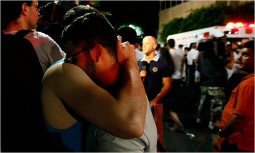 Israelis comfort each other at the scene of Saturday's killings
